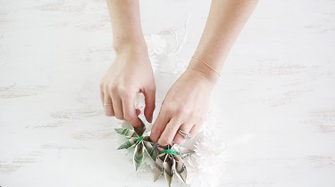 Tying money flowers to lei with pipe cleaners