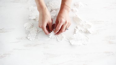 Stringing paper flowers together with a needle