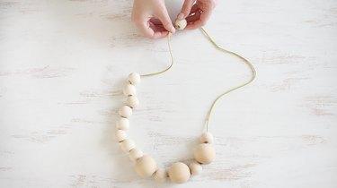 String wood beads onto ribbon