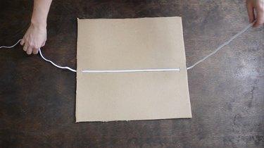 Pulling elastic string through slits in cardboard