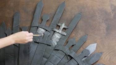 Dry brush silver paint onto swords