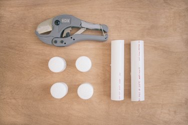 Two PVC pipes, four PVC caps, and a PVC pipe cutter