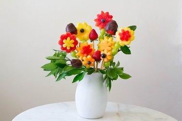 DIY edible fruit flower arrangement in white vase on table