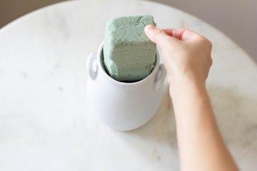 Pressing block of floral foam into vase