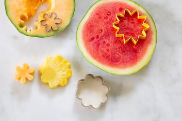 Cookie cutters cutting out flowers shapes in sliced watermelon and cantaloupe discs