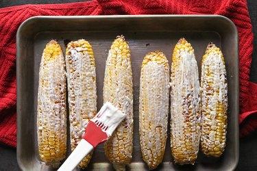 Brush sauce on corn