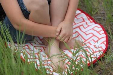 A child seated on a red and white DIY seat cushion, on a grassy lawn