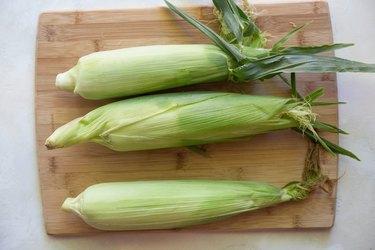 3 corn on the cobb on a cutting board.