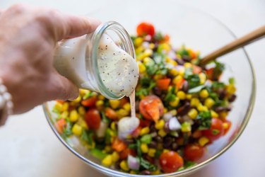 Pouring poppy seed dressing into salad bowl