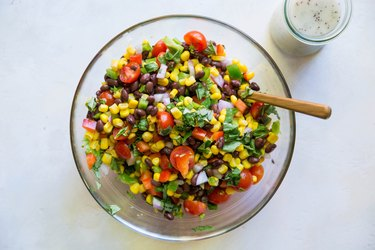 Corn salad in a bowl with dressing on side