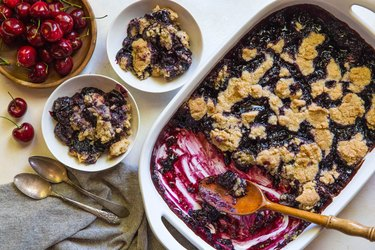 Two bowls and a casserole dish with cherry cobbler
