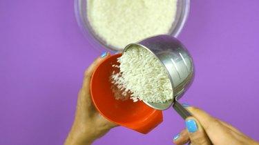 "Adding rice to bottle for DIY ""I Spy"" Bottle Travel Toy"