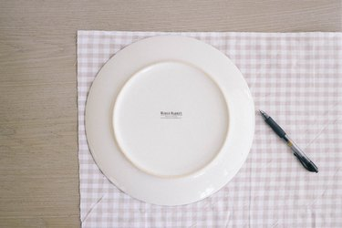 Tracing dinner plate on gingham fabric