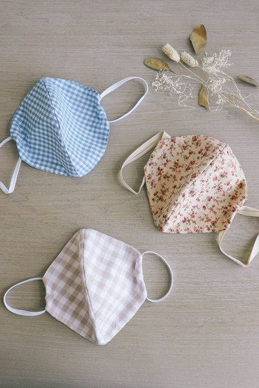 Three fabric DIY face masks in gingham and floral patterns