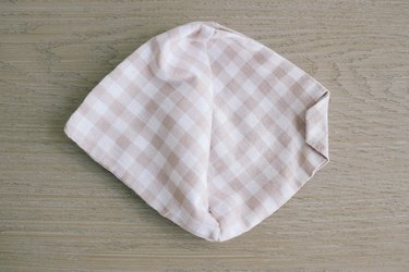 Folding in 1/4-inch on one side of the face mask