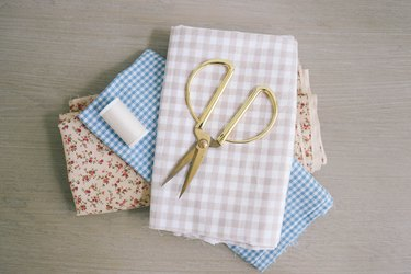 Gingham and floral fabric folded with gold scissors