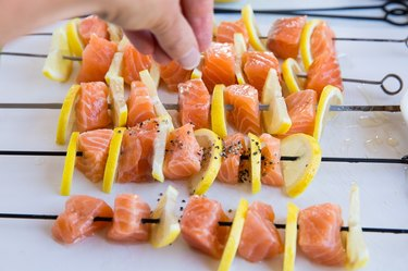 salmon kabobs being sprinkled with pepper