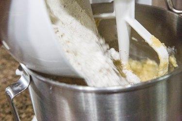pouring flour into a mixer