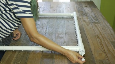 Inserting shower curtain tension rod into PVC frame for DIY PVC Pipe Pet Gate