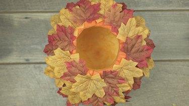 Decorating DIY Pumpkin Keg with fabric leaves