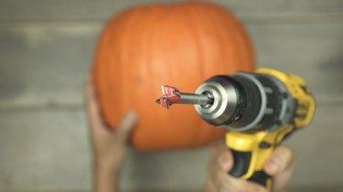 Using Forstner drill bit to cut a hole into a pumpkin to make DIY Pumpkin Keg