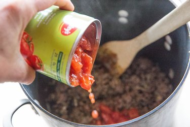 pouring diced tomatoes into a pot