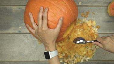 Scoop out pumpkin to make DIY Pumpkin Keg