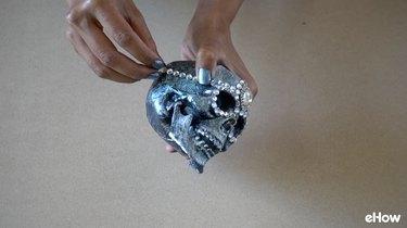 Applying gemstone strips to plastic skull for DIY Gemstone Studded Halloween Skull