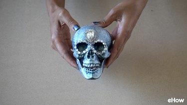 Applying gemstone strip around eyes of plastic skull for DIY Gemstone Studded Halloween Skull