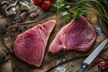 Two raw tuna steaks on rustic wooden table