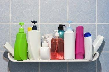 Many shampoo and soap bottles on a bathroom shelf