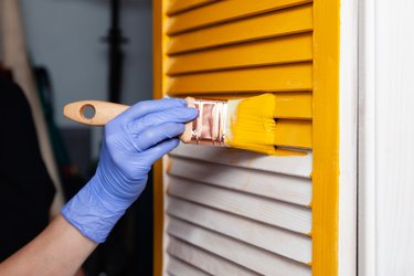 Closeup woman hand in purple rubber glove with paint brush painting natural wooden door with yellow paint, creative design house renovation theme. How to Paint Wooden Surface. Selected focus