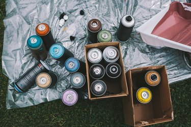 High Angle View Of Spray Paints On Floor