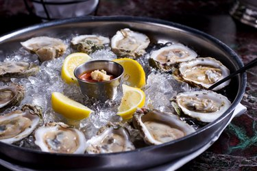 Fresh raw oysters with lemons on ice in metal tray