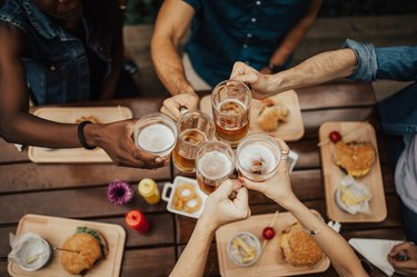 Five hands clinking beer mugs and glasses over pub food