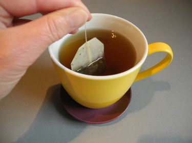 Cropped Hand Dipping Teabag In Cup At Home