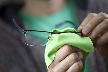 Midsection Of Man Cleaning Eyeglasses