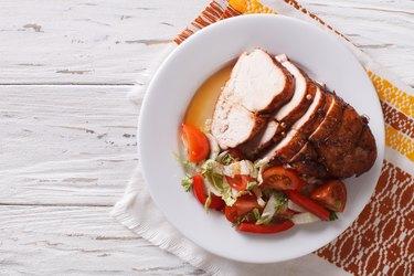 Sliced roasted turkey breast and fresh vegetables. Horizontal