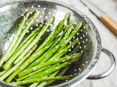 Washed asparagus in a metal colander on a kitchen table. Preparation vegetarian healthy food.