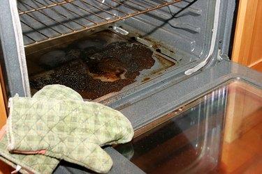 Oven door open, revealing blackened, baked-on spills
