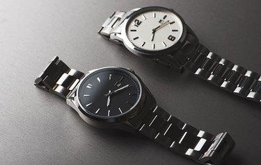 Two metallic wristwatches on gray background. Horizontal studio shot.