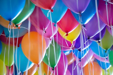 festive, colorful balloons with helium attachment to the white ribbons