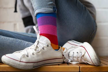 Woman sitting with her white sneakers and colored socks.