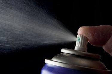 Spraying aerosol can isolated in black
