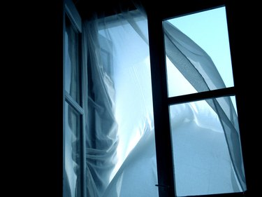 An open window in silhouette, with a curtain blowing outwards
