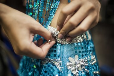 Young Woman Securing Sequined Dress With Safety Pin