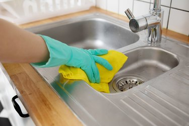 Close-Up Of Woman Hand Cleaning Kitchen Sink