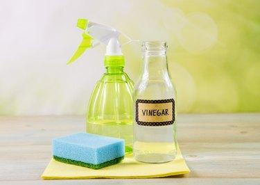 Vinegar, spray bottle and sponge