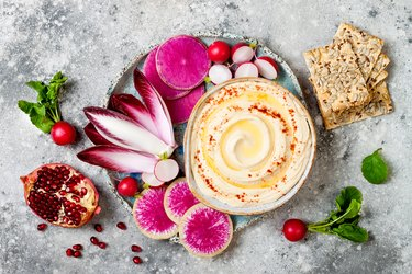 Homemade hummus seasoned with olive oil and paprika and fresh vegetables: radishes, watermelon radish, red chicory, pomegranate. Healthy vegetarian appetizer or snack platter