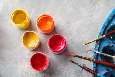 Jars with paints and brushes on table
